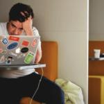 Mann sitzt vor Macbook