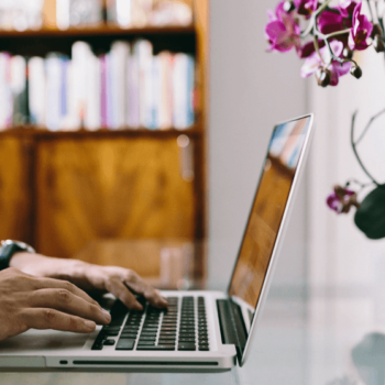 Mann arbeitet am Macbook am Glastisch und Orchidee