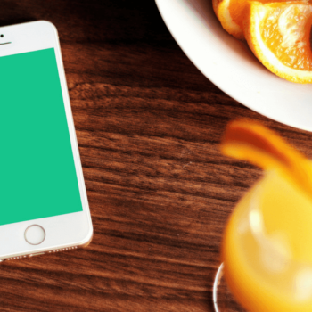 Smartphone mit grünem Obst und Obstschale daneben