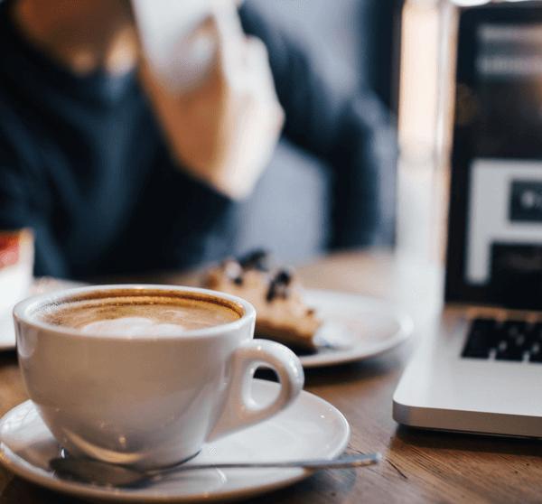 im Café mit Cappuccino, Kuchen und Macbook
