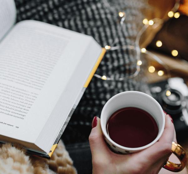 Frau liest ein Buch mit Teetasse in der Hand