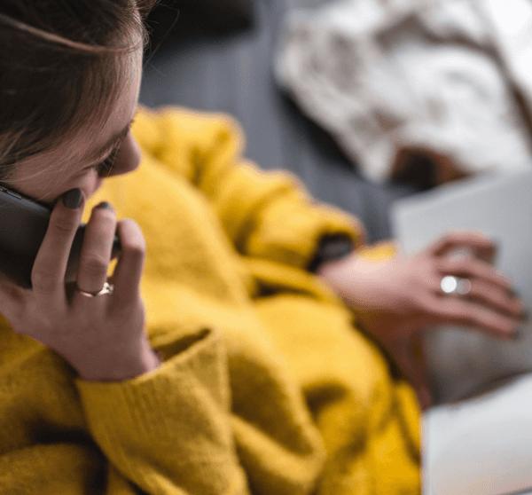 Frau sitzt auf der Couch, liest ein Buch und telefoniert