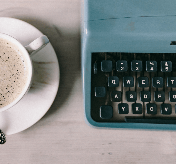 weißer Holztisch mit einer Tasse Kaffee und Schreibmaschine