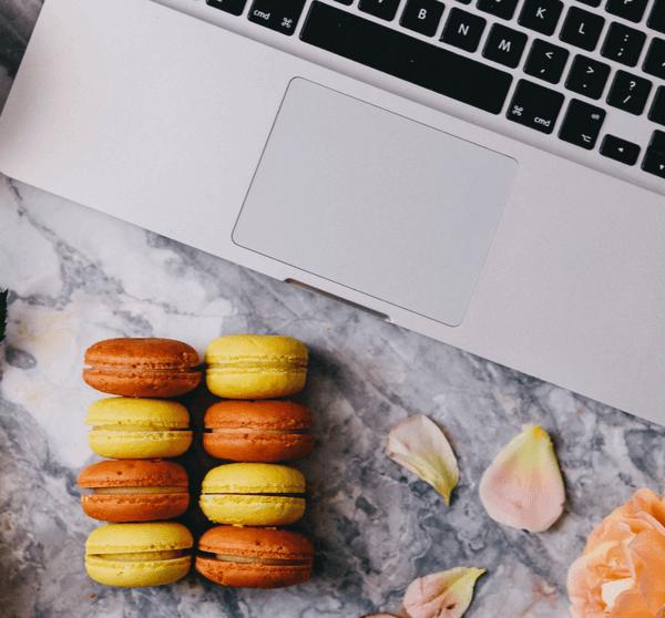 Marmortisch auf dem ein Macbook, Blumen, eine Kaffeetasse und Macarons liegen