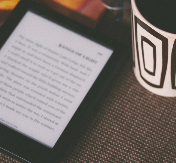 eBook Reader mit Notizheft und Kaffeetasse
