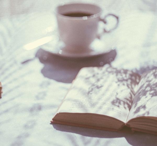 ein Stapel Bücher, ein aufgeschlagenes Buch mit Kaffeetasse im Hintergrund