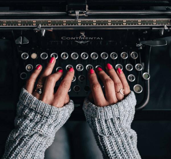 Frau mit roten Fingernägeln tippt auf einer alten Vintage Schreibmaschine
