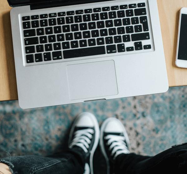 Holztisch auf dem ein Macbook und iPhone liegt