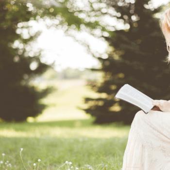 Frau sitzt auf einem Stein mittten in einer grünen Wiese mit Bäumen im Hintergrund und liest ein Buch
