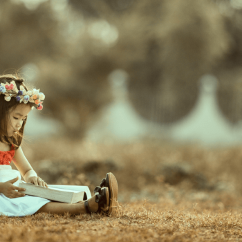 Mädchen mit Blumenkranz im Haar liest ein Buch und sitzt auf einer Wiese