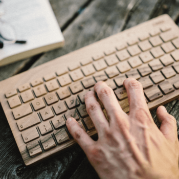 Mann tippt auf einer Holztastatur mit Buch und Brille im Hintergrund