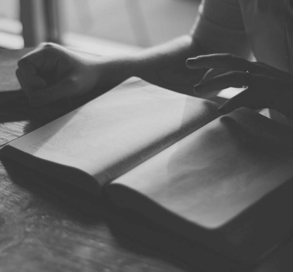 schwarzweiß Bild mit offenem Buch und Kaffeetasse