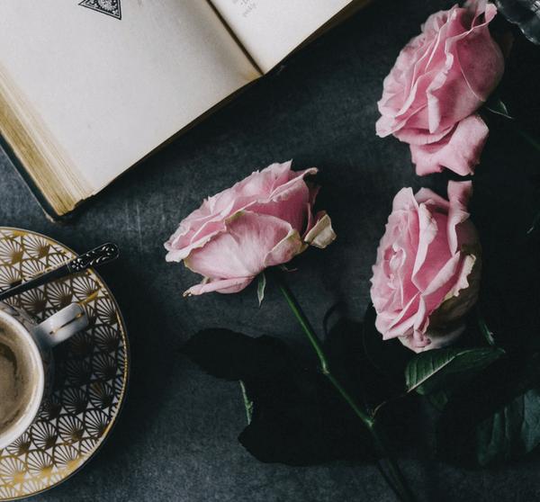 Kaffeetasse, rosa Rosen und geöffnetes Buch auf dunklem Hintergrund