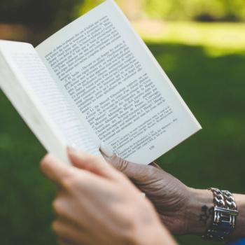 Frau hält Buch in der Hand mit grüner Wiese im Hintergrund