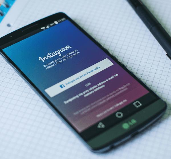 Smartphone mit offener Instagram App liegt auf Notizblock und Stift