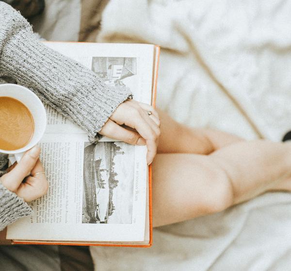 Frau sitzt mit geöffnetem Buch und Kaffetasse in der Hand