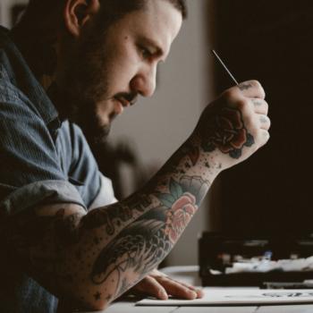 Künstler mit tätowierten Armen sitzt vor seinem Schreibtisch