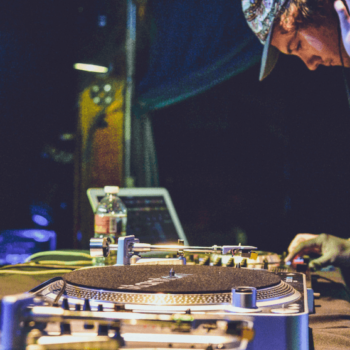 DJ steht am DJ Pult