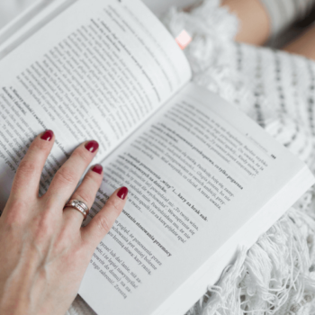 Frau liest zugedeckt ein Buch