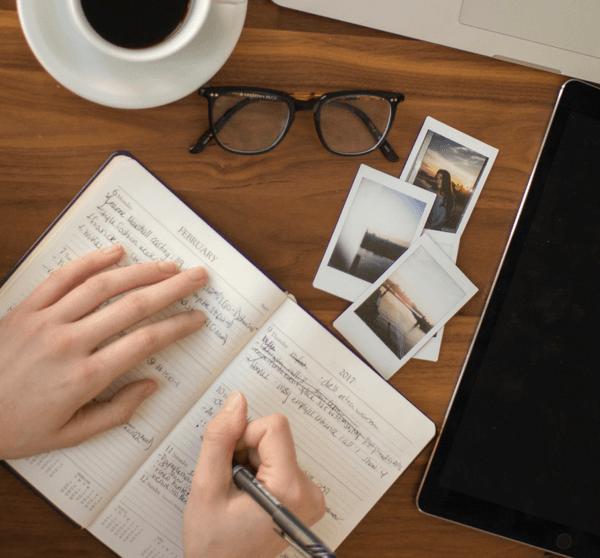 Frau schreibt in ihrem Kalender