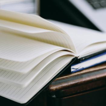 geöffnetes Notizbuch liegt auf Schreibtisch