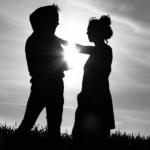 Schwarz-weiß Foto von Pärchen vor bewölktem Himmel