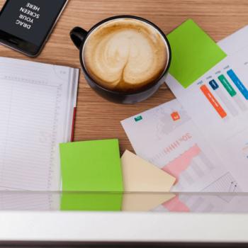 Papiere und Kalender liegen auf Tisch mit Cappuccino