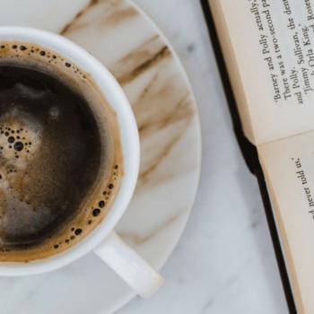 Kaffeetasse und geöffentes Buch liegen auf Marmortisch