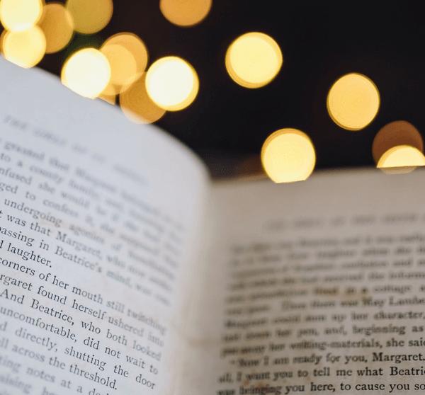 geöffnetes Buch vor schwarzem Hintergrund