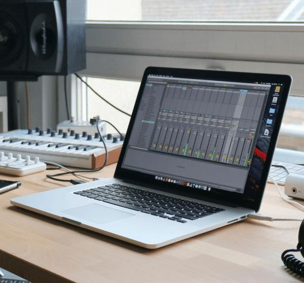 Macbook mit Kopfhörern und Musikequipment