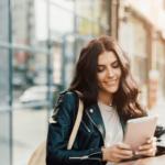 Frau mit schwarzer Lederjacke liest auf einem Tablet